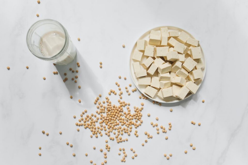 Tofu on a plate surrounded by soybeans and next to a glass of soy milk